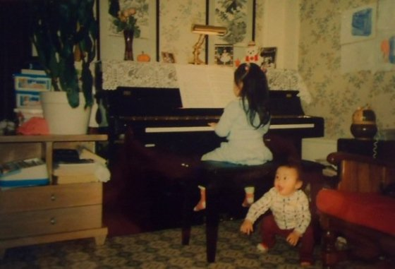 Practicing piano (and that's my brother being silly)!